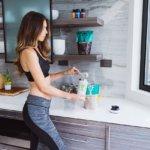 Sportliche Frau mischt sich veganes Proteinpulver